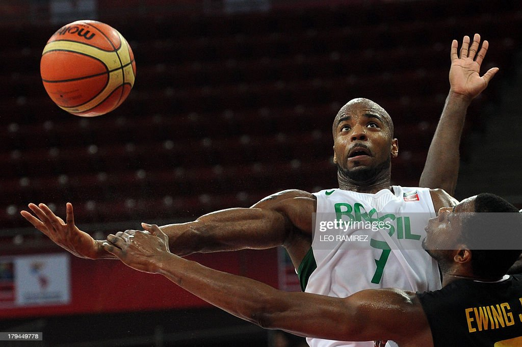 Brazilian Larry Taylor (top) vies for the ball with Jamaican Patrick Ewing during their Spain 2014 FIBA World Cup qualifier game in Caracas on September 3, 2013. AFP PHOTO/ Leo RAMIREZ