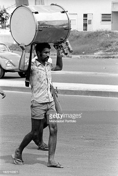 Brazilian man carrying a musical instrument on his head Rio de Janeiro May 1977