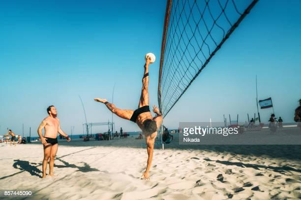 Brasilianischen Mann springen und treten Kugel am Strand in Brasilien