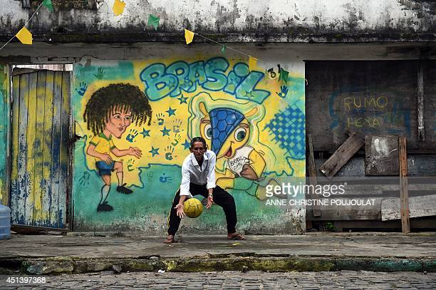 A Brazilian man plays football in Porto Seguro on June 28 during the Round of 16 football match between Brazil and Chile played at the Mineirao...