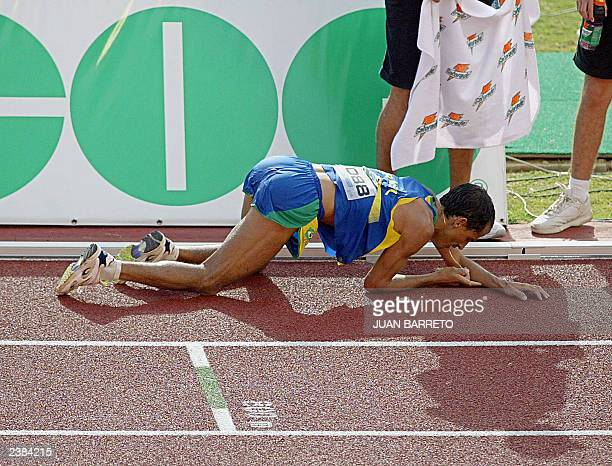 Brazilian marathonist Vanderlei Lima collapses of exhaustion after crossing the finish line winning the Gold medal clocking 2H1907 09 August 2003...