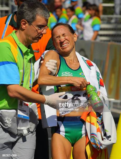 Brazilian Marcia Narloch is helped by an assitant as she shows the pain after crossing the finish line of the women´s marathon in second place 22...