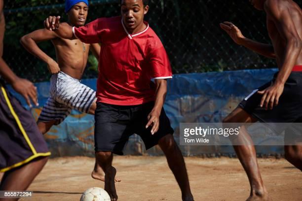 4 Brazilian men playing football in a favela of Rio