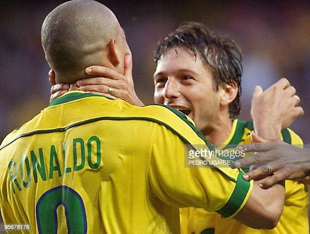 Brazilian midfielder Leonardo and forward Ronaldo who scored twice celebrate during the 1998 Soccer World Cup second round match between Brazil and...