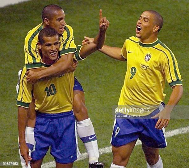 Brazilian midfielder Rivaldo and Roberto Carlos is congratulated by striker Ronaldo after he scored for his team during the 1998 Soccer World Cup...