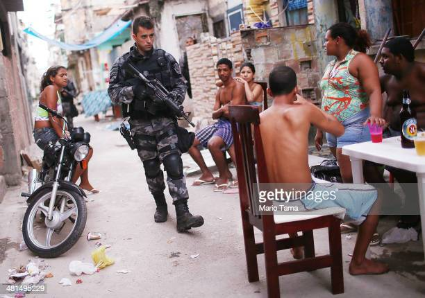 Brazilian military police officer patrols after entering the unpacified Complexo da Mare one of the largest 'favela' complexes in Rio on March 30...