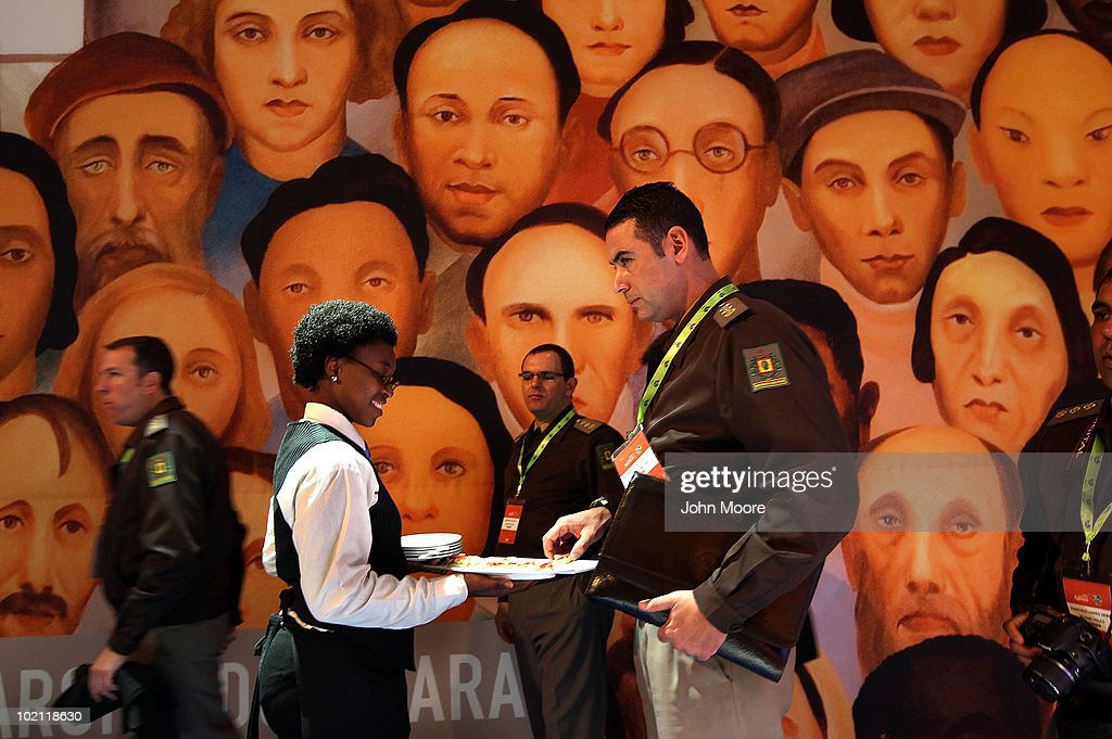 A Brazilian military policeman takes an hors d'oeuvre from a South African waitress at the opening of the Brazil Sensational expo on June 15, 2010 in Sandton, South Africa. Brazil opened the exhibit at the Sandton Convention Center, showing off Brazilian culture, provincial art and its distinguished soccer history as a record five-time World Cup champion. The Brazilian military police are in South Africa doing research in preparation for hosting the 2014 FIFA World Cup in Brazil. The painting was by leading Brazilian modernist artist Tarsila do Amaral.