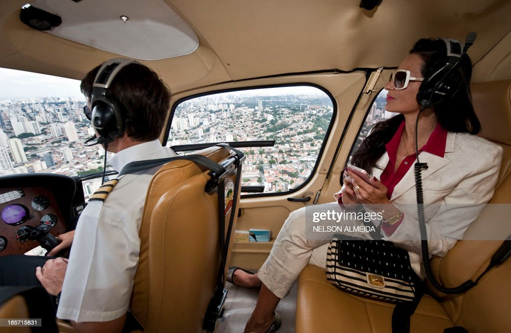 Brazilian millionaire Cozete Gomes (R) checks her cellphone as she flies on her helicopter over Sao Paulo, on April 4, 2013. Cozete Gomes owns eight companies in the sector of promotional events, assignment of temporary labor, outsourcing of labor and services, recruitment and selection, training and events, which last year grossed about 100 million reais (US dollars 50,3 millions). AFP PHOTO / Nelson ALMEIDA