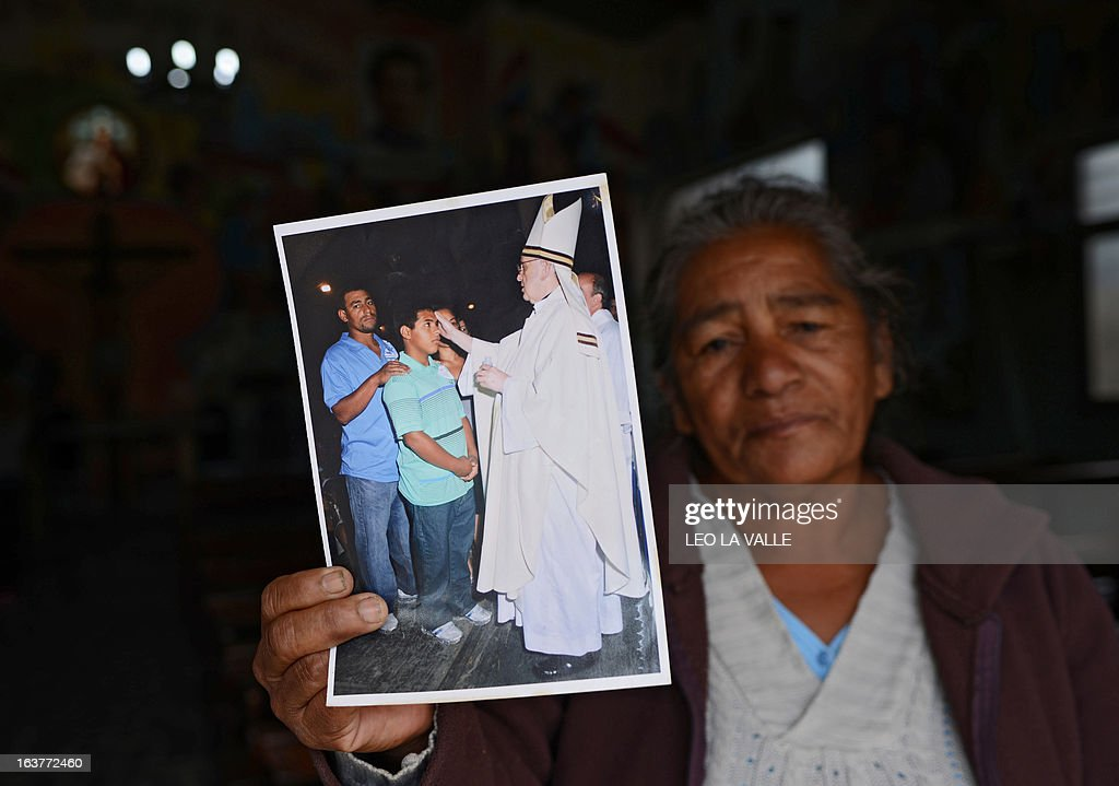 Brazilian missionary Eva Camila shows a picture of her son Julio and her grandson Ruben with Pope Francis I inside the Virgen de Caacupe chapel at Villa 21-24 on March 15, 2013 outside the Virgen of Caacupe chapel. Pope Francis used to visit the neighbourhood when he was bishop in Buenos Aires . AFP PHOTO/Leo La Valle
