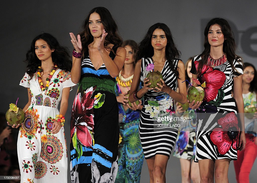Brazilian model Adriana Lima (2ndL) applauds as she presents a creation by Desigual with other models during the 080 Barcelona fashion on July 9, 2013 in Barcelona.