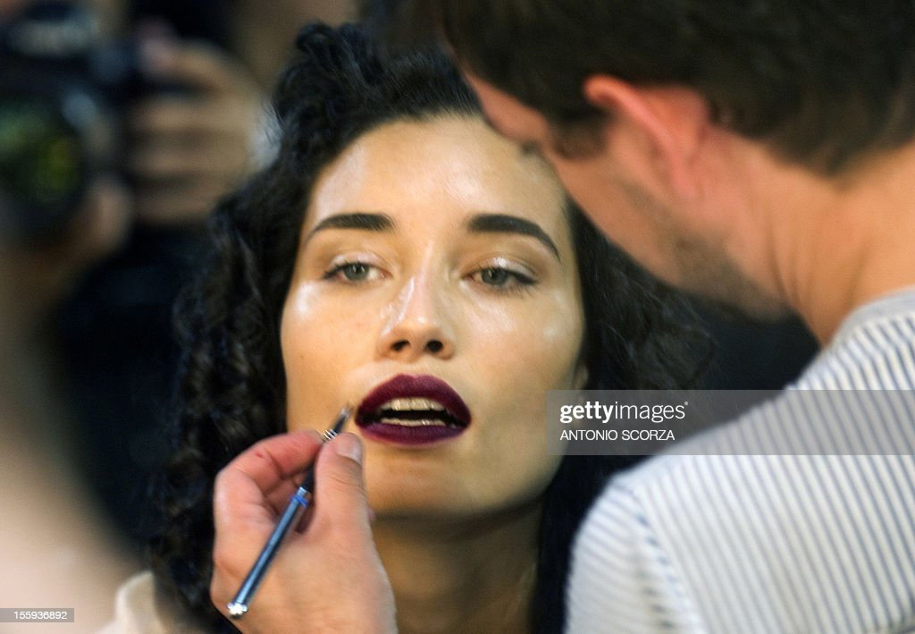 A Brazilian model has her make-up done before the start of the Nica Kessler presentation within the Rio Fashion Week 2013 Autumn/ Winter collection on November 9, 2012 in Rio de Janeiro, Brazil. AFP PHOTO / ANTONIO SCORZA