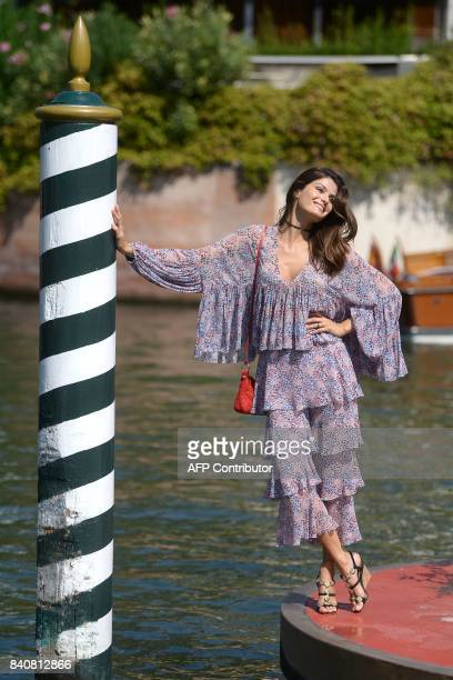 Brazilian model Isabeli Fontana poses for photographers as she arrives at the Excelsior Hotel during the 74th Venice Film Festival on August 30 2017...