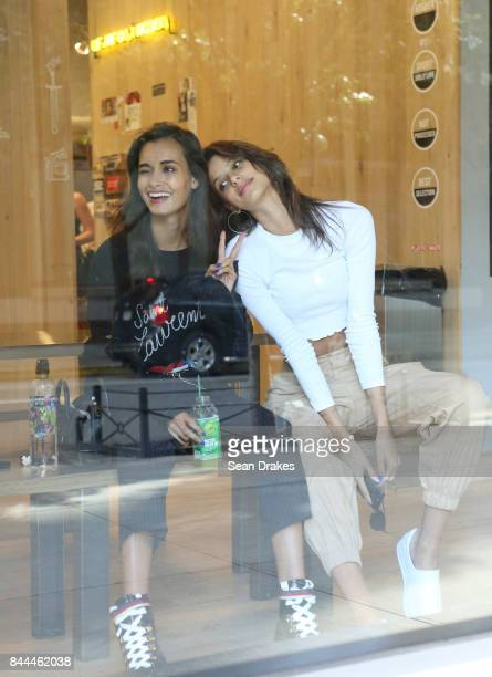 Brazilian models Gizele Oliveira and Bruna Lirio sit in a juice bar after walking in fashion shows at Skylight Clarkson Square in SoHo during New...