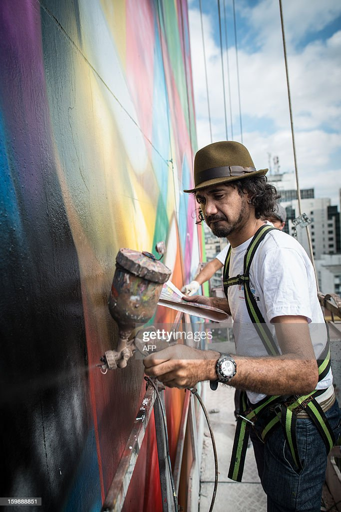 Brazilian mural artist Eduardo Kobra (front) and his assistants paint the side of a 56-meter high building, portraying Brazilian architect Oscar Niemeyer who passed away last December at the age of 104, along Paulista avenue in Sao Paulo, Brazil on January 22, 2013. Internationaly renown Kobra started to negotiate to paint the building 5 years ago and now, financially supported by the building management, Kobra paints voluntarily ahead of the commemoration of the city's 459th anniversary next January 25. AFP PHOTO/Yasuyoshi CHIBA
