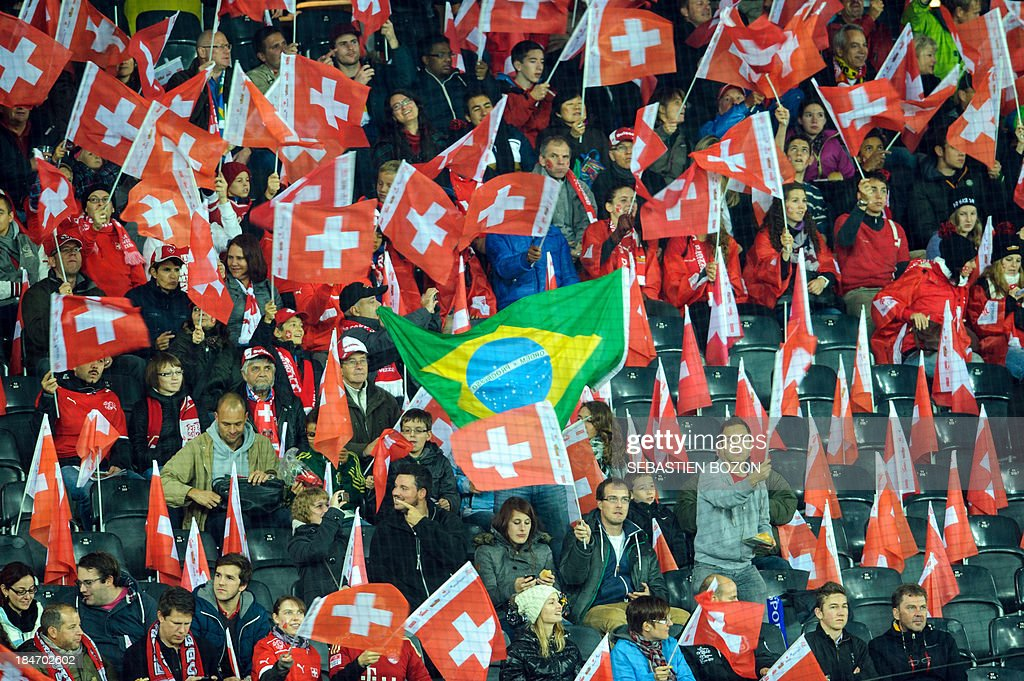 A Brazilian national flag is seen among Swiss flags during the world cup 2014 qualification match Switzerland vs Slovenia on October 15, 2013, at the Stade de Suisse in Bern.