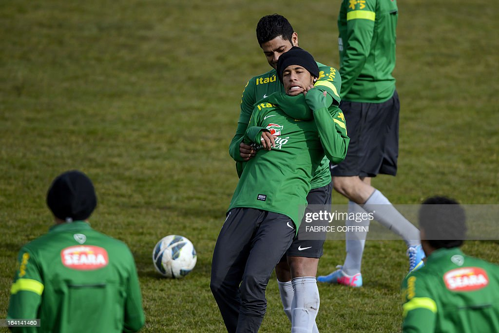Brazilian national football team forward Hulk (up) plays with Brazilian forward Neymar during a training session on March 20, 2013 in Nyon, on the eve of a friendly football match against Italy in Geneva.