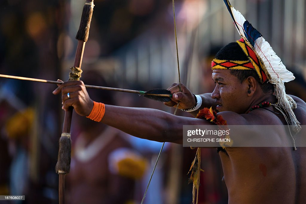 A Brazilian native from the Pataxo ethnic group takes part in the bow and arrow competition, during the first day of the International Games of Indigenous Peoples, in Cuiaba, state of Mato Grosso, on November 10, 2013. 1500 natives from 49 Brazilian ethnic groups and from another 17 countries are gathering in Cuiaba until November 16 to compete in some 30 athletic disciplines, many of their own. AFP PHOTO / Christophe Simon
