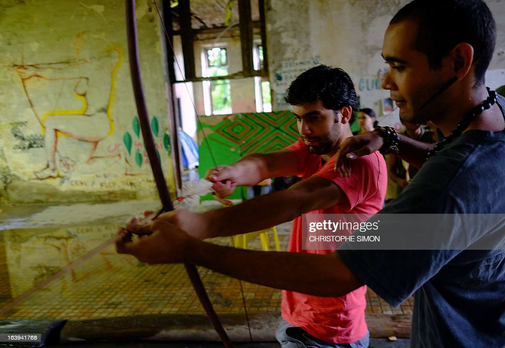 A Brazilian native (R) teaches an activist how to use a bow, in the former Indigenous Museum --aka Aldea Maracana-- next to the Maracana stadium in Rio de Janeiro on March 18, 2013. Indigenous people have been occupying the place since 2006, which is due to be pulled down to construct 10,500 parking lots for the upcoming Brazil 2014 FIFA World Cup.