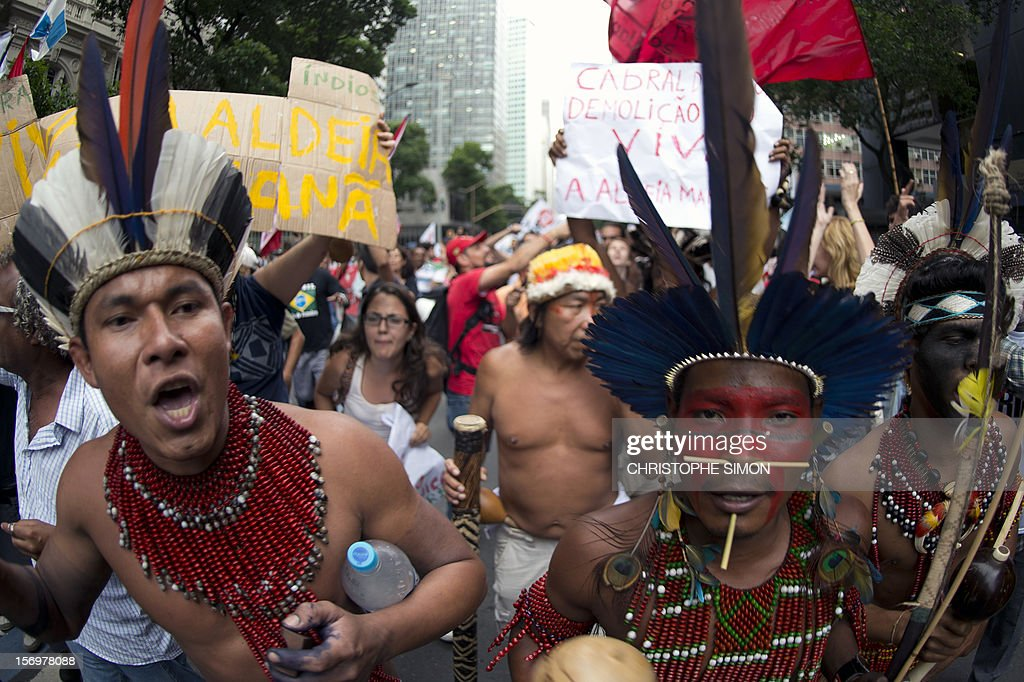 Brazilian natives occupying the old indigenous museum next to the Maracana stadium, hold an own protest, as thousands demonstrate demanding Brazilian President Dilma Roussef to veto a bill that would redistribute oil royalties in favor of non-oil producing states, in Rio de Janeiro, Brazil, on November 26, 2012. Both Rio de Janeiro's mayor Eduardo Paes and governor Sergio Cabral warned that the new oil royalties share-out plan will jeopardize the financing of the 2014 World Cup and the 2016 summer Olympics. AFP PHOTO/Christophe Simon
