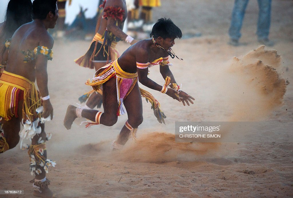 Brazilian natives of the Pareci tribe celebrate throwing sand while playing head football with a hand-made ball for a demonstration, during the first day of the International Games of Indigenous Peoples, in Cuiaba, state of Mato Grosso, on November 10, 2013. 1500 natives from 49 Brazilian ethnic groups and from another 17 countries are gathering in Cuiaba until November 16 to compete in some 30 athletic disciplines, many of their own. AFP PHOTO / Christophe Simon
