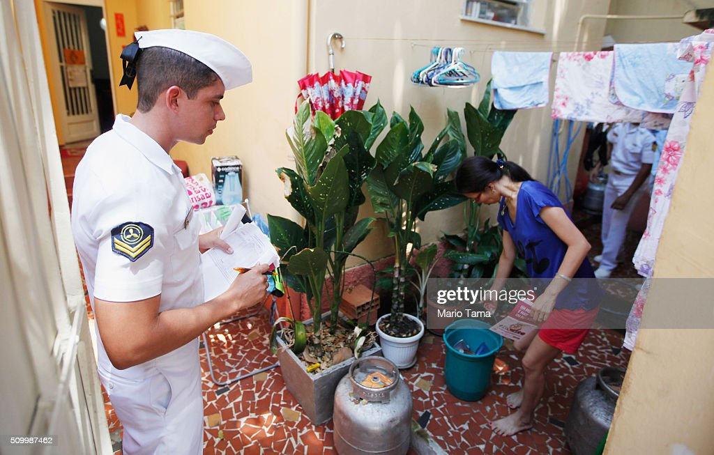 Brazilian Navy sailor inspects a woman's home while warning of the dangers of the Zika virus and how to protect against mosquitos on February 13, 2016 in Rio de Janeiro, Brazil. 220,000 Brazilian military troops were deployed today in a mobilization across country to warn of the dangers of the mosquito-borne virus which may be linked to microcephaly.