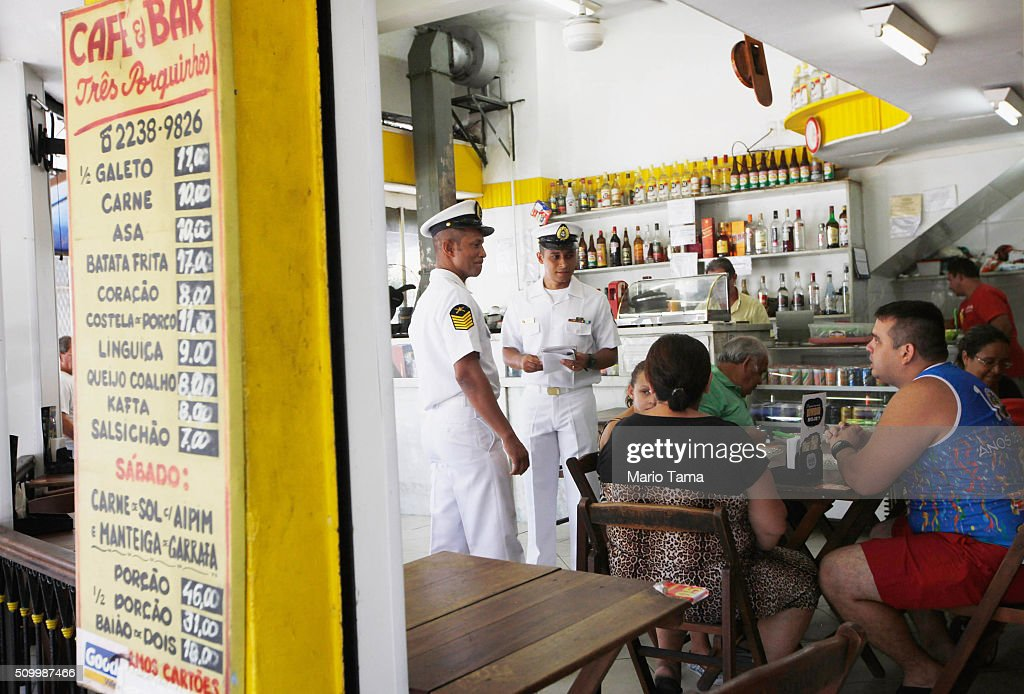 Brazilian Navy sailors chat to people in a restaurant while passing out pamphlets warning of the dangers of the Zika virus and how to protect against mosquitos on February 13, 2016 in Rio de Janeiro, Brazil. 220,000 Brazilian military troops were deployed today in a mobilization across country to warn of the dangers of the mosquito-borne virus which may be linked to microcephaly.