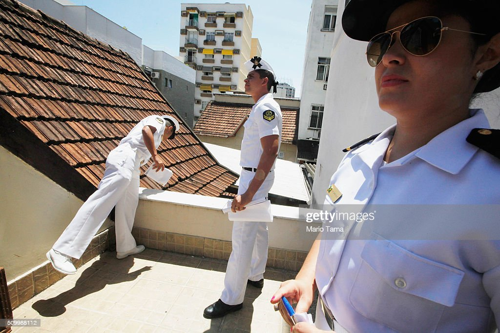 Brazilian Navy sailors inspect a home for potential mosquito breeding sites while passing out pamphlets warning of the dangers of the Zika virus and how to protect against mosquitos on February 13, 2016 in Rio de Janeiro, Brazil. 220,000 Brazilian military troops were deployed today in a mobilization across country to warn of the dangers of the mosquito-borne virus which may be linked to microcephaly.