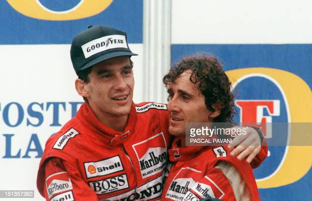 Brazilian new formula one champion Ayrton Senna embraces his teammate and winner of today Adelaide Australian Grand Prix French driver Alain Prost on...