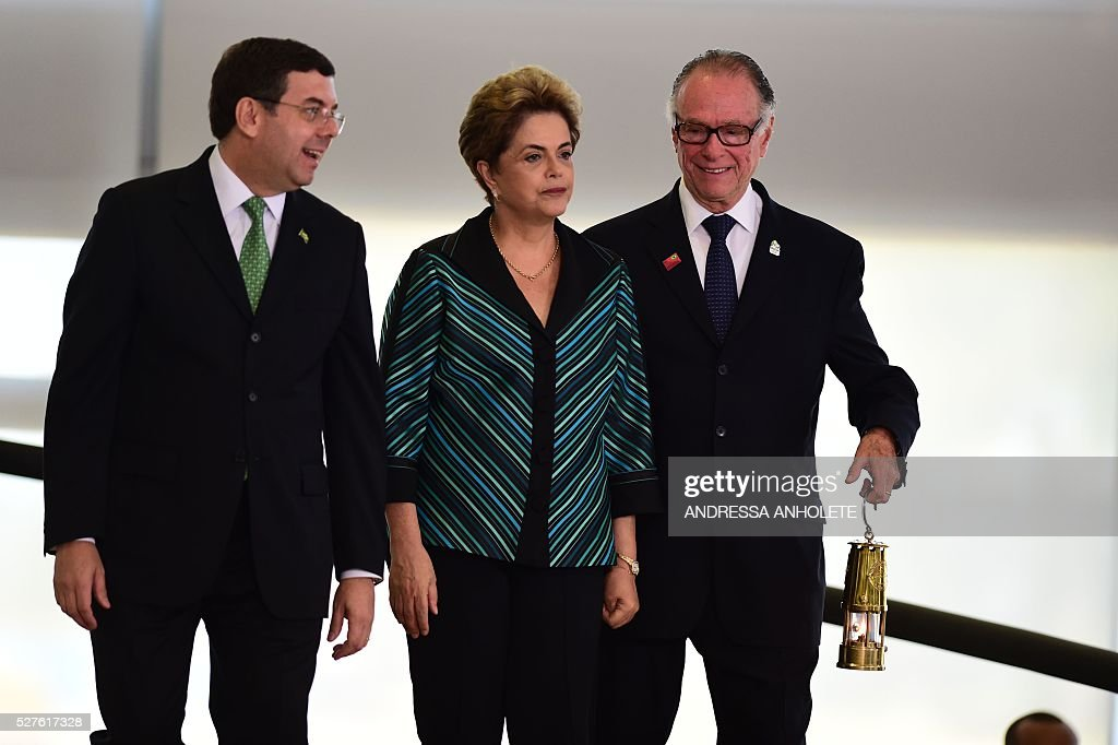 Brazilian Olympic Committee President Carlos Arthur Nuzman (R) carries the Olympic flame as he heads with Brazilian President Dilma Rousseff (C) and Brazilian Sports Minister Ricardo Leyser to a ceremony at Planalto Palace in Brasilia following the flame's arrival in Brazil on May 3, 2016 ahead of the Rio 2016 Olympic Games in August. The Olympic flame arrived in Brasilia May 3 aboard a flight from Geneva to embark on a procession across Brazil culminating in the opening ceremony of the 2016 Games in Rio de Janeiro. The torch will travel to more than 300 towns and cities carried by some 12,000 relay runners before arriving August 5 at the mythic Maracana stadium to kick off the first Olympics in South America. / AFP / ANDRESSA