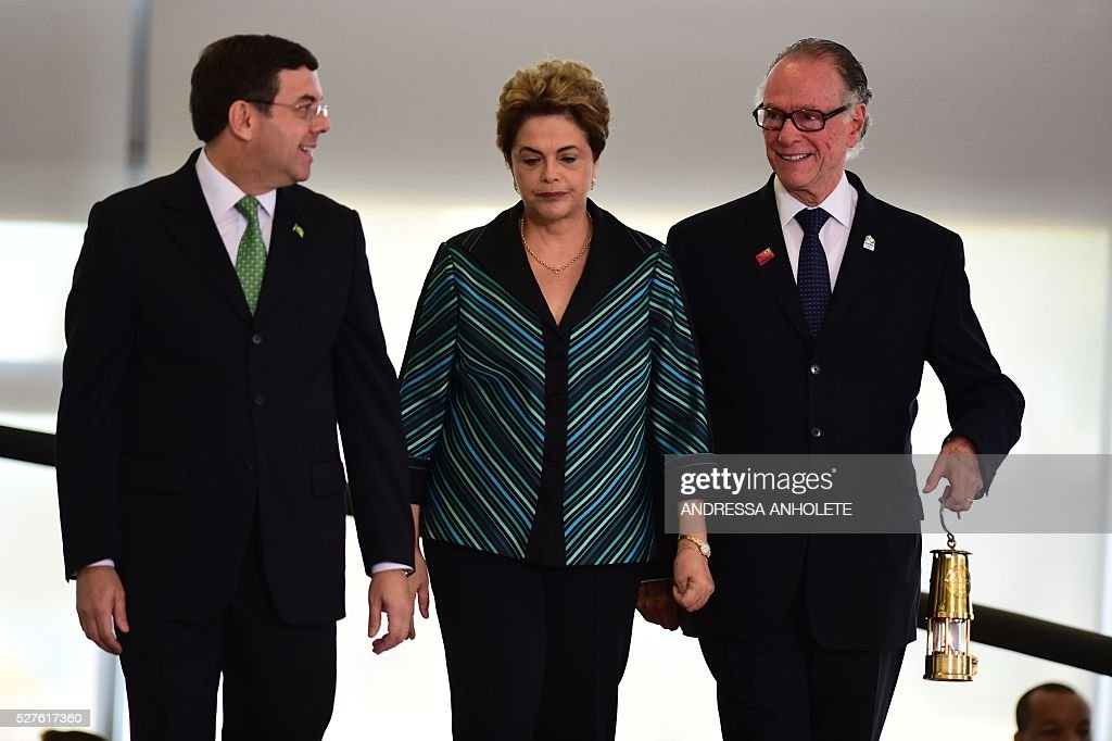 Brazilian Olympic Committee President Carlos Arthur Nusmann (R) carries the Olympic flame as he heads with Brazilian President Dilma Rousseff (C) and Brazilian Sports Minister Ricardo Leyser to a ceremony at Planalto Palace in Brasilia following the flame's arrival in Brazil on May 3, 2016 ahead of the Rio 2016 Olympic Games in August. The Olympic flame arrived in Brasilia May 3 aboard a flight from Geneva to embark on a procession across Brazil culminating in the opening ceremony of the 2016 Games in Rio de Janeiro. The torch will travel to more than 300 towns and cities carried by some 12,000 relay runners before arriving August 5 at the mythic Maracana stadium to kick off the first Olympics in South America. / AFP / ANDRESSA