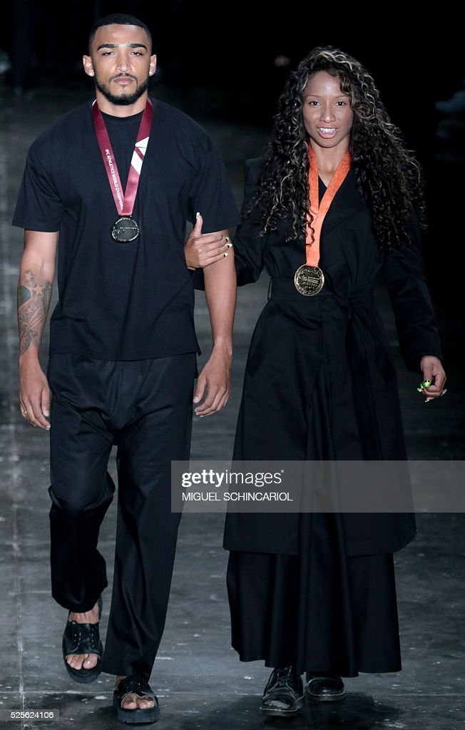 Brazilian paralympian athlete Silvania Costa (R) presents creations by Joao Pimenta during the 2017 Summer collections of the Sao Paulo Fashion Week in Sao Paulo, Brazil on April 28, 2016. / AFP / Miguel Schincariol