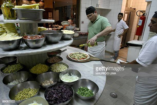 Brazilian 'pizzaiolo' Joao Silva Martins who makes around 600 pizzas per night is helped by an assistant as he gets a pizza ready for the oven at a...