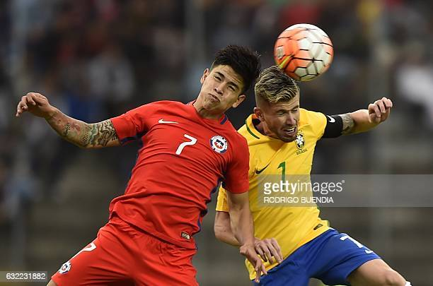 Brazilian player Ciao vies for the ball with Chile's Victor Davila during their South American Championship U20 football match in the Olimpico...