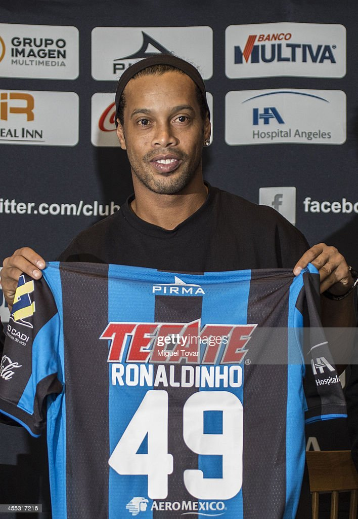 Brazilian player <a gi-track='captionPersonalityLinkClicked' href=/galleries/search?phrase=Ronaldinho&family=editorial&specificpeople=202667 ng-click='$event.stopPropagation()'>Ronaldinho</a> Gaucho poses for pictures holding his jersey #49 during a press conference to unveil as a new player at Camino Real Hotel on September 12, 2014 in Mexico City, Mexico.