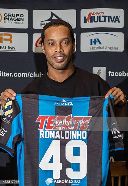 Brazilian player Ronaldinho Gaucho poses for pictures holding his jersey during a press conference to unveil as a new player at Camino Real Hotel on...