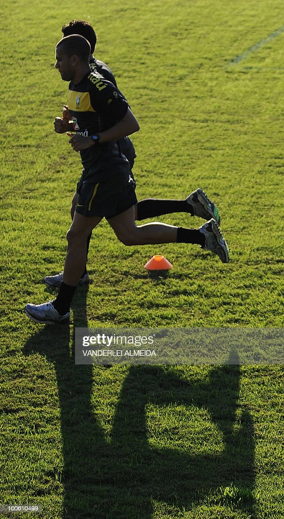 Brazilian players Daniel Alves and Josue jog during the last day of training in the southern Brazilian city of Curitiba on May 25, 2010. Brazil, five-time world champion, is among the favourites for the South Africa 2010 World Cup which starts on June 11th. AFP PHOTO/Vanderlei ALMEIDA