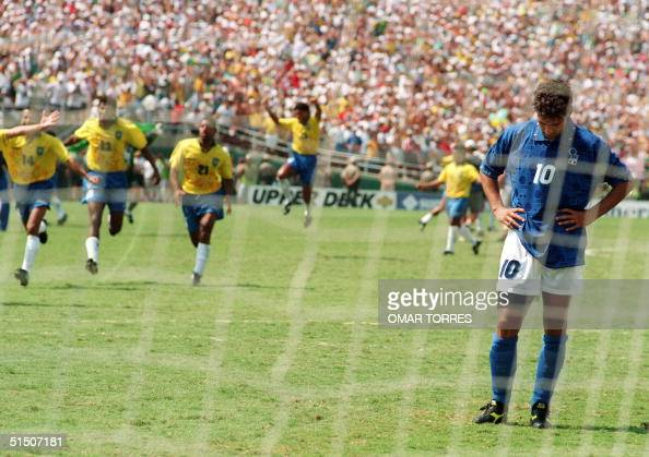 Brazilian players run to join their teammates as Italian midfielder Roberto Baggio bows his head after he missed his penalty kick giving Brazil a 32...