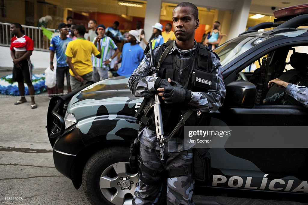 Brazilian policeman guards the street during the Carnival parade in the favela of Rocinha, on 20 February 2012 in Rio de Janeiro, Brazil. Rocinha, the largest shanty town in Brazil and one of the most developed in Latin America, has its own samba school called GRES Academicos da Rocinha. The Rocinha samba school is very loyal to its neighborhood. Throughout the year, the entire community actively participate in rehearsals, culture events and parades related to the carnival.