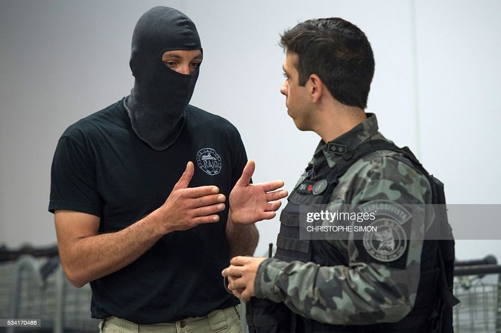 A Brazilian policeman (R) of the BAC (Brigade of canine action) special unit speaks with a French RAID (Research, Assistance, Intervention, Deterrence) policeman (masked) as they train a dogs for the research of explosives at the Tom Jobim international airport in Rio de Janeiro, Brazil on 25 May, 2016. Two members of the French RAID police shared their techniques with the Brazilian police two months ahead of the Rio Olympic Games. / AFP / CHRISTOPHE