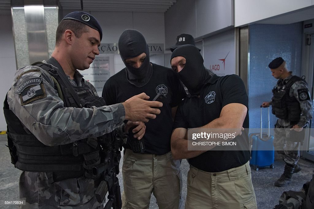 A Brazilian policeman (L) of the BAC (Brigade of canine action) special unit speaks with French RAID (Research, Assistance, Intervention, Deterrence) policemen (masked) as they train a dogs for the research of explosives at the Tom Jobim international airport in Rio de Janeiro, Brazil on 25 May, 2016. Two members of the French RAID police shared their techniques with the Brazilian police two months ahead of the Rio Olympic Games. / AFP / CHRISTOPHE