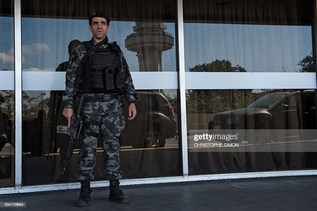 A Brazilian policeman of the BAC (Brigade of canine action) special unit stands guard at the Tom Jobim international airport in Rio de Janeiro, Brazil on 25 May, 2016. Two members of the French RAID (Research, Assistance, Intervention, Deterrence) police shared their techniques with the Brazilian police two months ahead of the Rio Olympic Games. / AFP / CHRISTOPHE