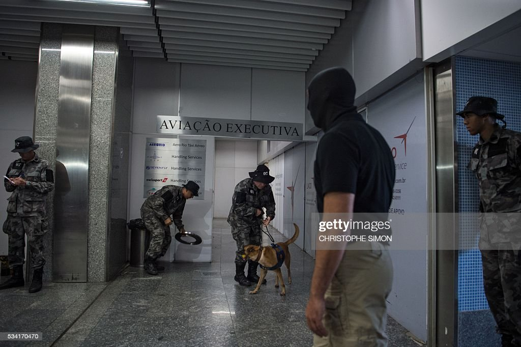 Brazilian policemen of the BAC (Brigade of canine action) special unit and a French RAID (Research, Assistance, Intervention, Deterrence) policeman (2-R) train a dog called 'Aba' for the research of explosives at the Tom Jobim international airport in Rio de Janeiro, Brazil on 25 May, 2016. Two members of the French RAID police shared their techniques with the Brazilian police two months ahead of the Rio Olympic Games. / AFP / CHRISTOPHE