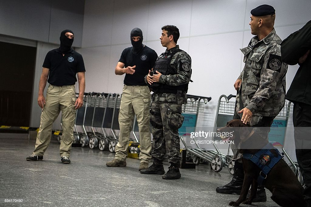 Brazilian policemen of the BAC (Brigade of canine action) special unit speak with French RAID (Research, Assistance, Intervention, Deterrence) policemen (masked) as they train a dog called 'Chefe' for the research of explosives at the Tom Jobim international airport in Rio de Janeiro, Brazil on 25 May, 2016. Two members of the French RAID police shared their techniques with the Brazilian police two months ahead of the Rio Olympic Games. / AFP / CHRISTOPHE
