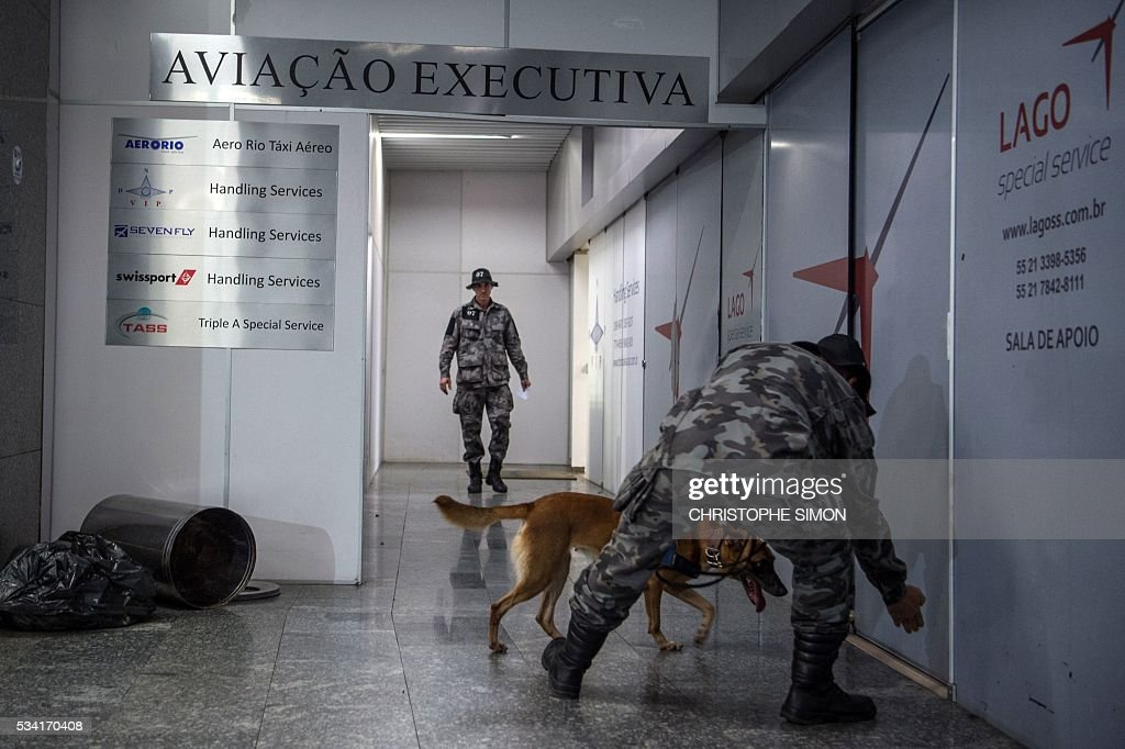 Brazilian policemen of the BAC (Brigade of canine action) special unit train a dog called 'Aba' for the research of explosives at the Tom Jobim international airport in Rio de Janeiro, Brazil on 25 May, 2016. Two members of the French RAID (Research, Assistance, Intervention, Deterrence) police shared their techniques with the Brazilian police two months ahead of the Rio Olympic Games. / AFP / CHRISTOPHE