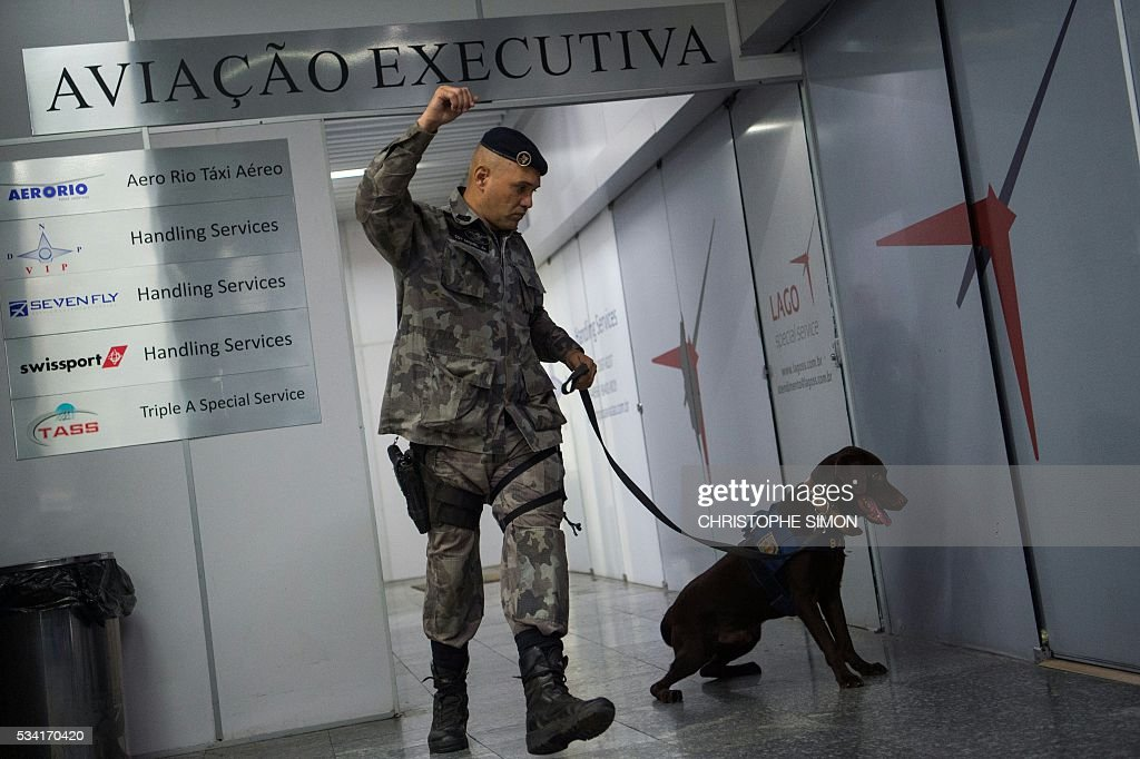 Brazilian policemen of the BAC (Brigade of canine action) special unit train a dog called 'Chefe' for the research of explosives at the Tom Jobim international airport in Rio de Janeiro, Brazil on 25 May, 2016. Two members of the French RAID (Research, Assistance, Intervention, Deterrence) police shared their techniques with the Brazilian police two months ahead of the Rio Olympic Games. / AFP / CHRISTOPHE