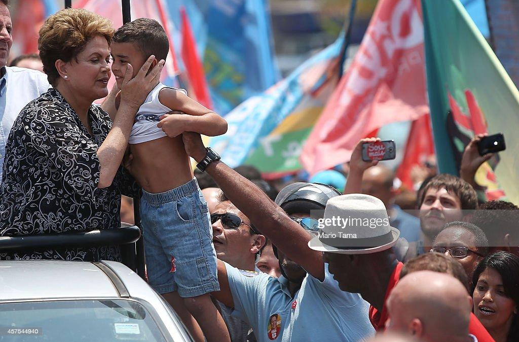 Brazilian president and presidential candidate of the Workers Party (PT) Dilma Rousseff (L) prepares to kiss a boy during a campaign visit in the Padre Miguel neighborhood on October 20, 2014 in the West Zone of Rio de Janeiro, Brazil. Rousseff is set to face Aecio Neves, presidential candidate for the Brazilian Social Democracy Party (PSDB), in a run-off election October 26.