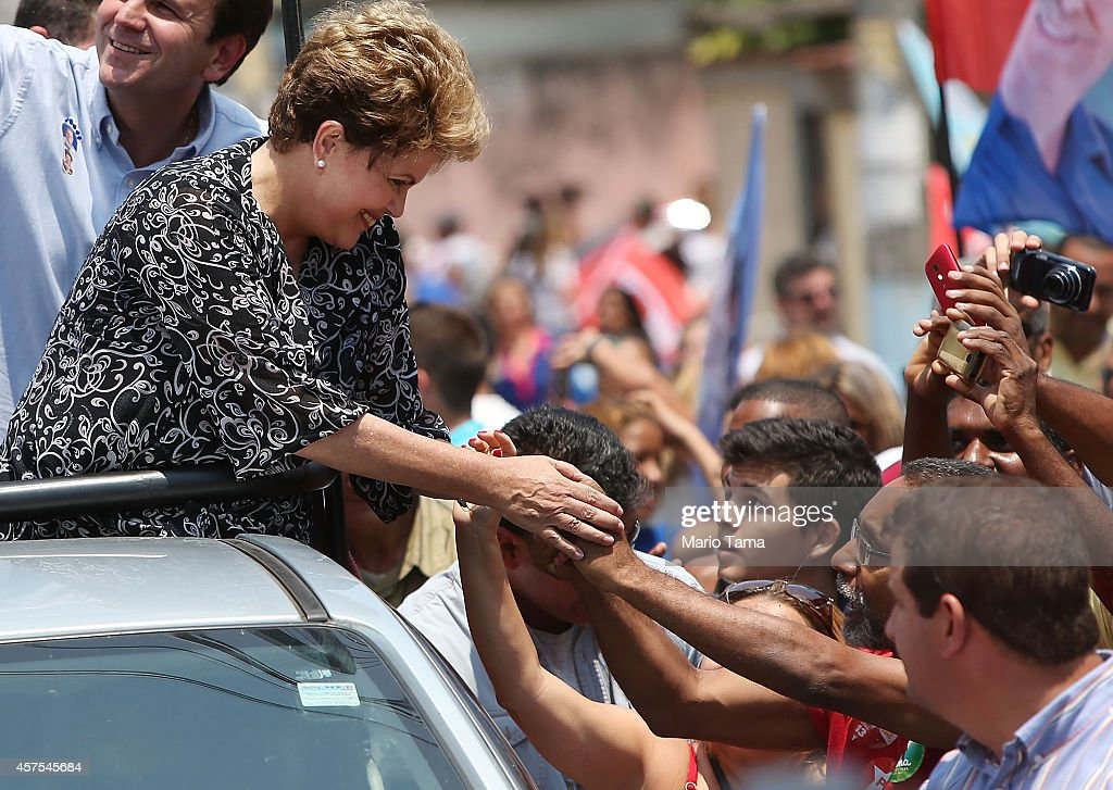 Brazilian president and presidential candidate of the Workers Party (PT) <a gi-track='captionPersonalityLinkClicked' href=/galleries/search?phrase=Dilma+Rousseff&family=editorial&specificpeople=1955968 ng-click='$event.stopPropagation()'>Dilma Rousseff</a> (L) greets supporters during a campaign visit in the Padre Miguel neighborhood on October 20, 2014 in the West Zone of Rio de Janeiro, Brazil. Rousseff is set to face Aecio Neves, presidential candidate for the Brazilian Social Democracy Party (PSDB), in a run-off election October 26.