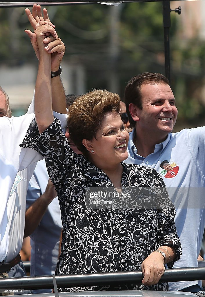 Brazilian president and presidential candidate of the Workers Party (PT) <a gi-track='captionPersonalityLinkClicked' href=/galleries/search?phrase=Dilma+Rousseff&family=editorial&specificpeople=1955968 ng-click='$event.stopPropagation()'>Dilma Rousseff</a> (L) and Rio de Janeiro Mayor <a gi-track='captionPersonalityLinkClicked' href=/galleries/search?phrase=Eduardo+Paes&family=editorial&specificpeople=5692531 ng-click='$event.stopPropagation()'>Eduardo Paes</a> (R) smile during a campaign visit in the Padre Miguel neighborhood on October 20, 2014 in the West Zone of Rio de Janeiro, Brazil. Rousseff is set to face Aecio Neves, presidential candidate for the Brazilian Social Democracy Party (PSDB), in a run-off election October 26.