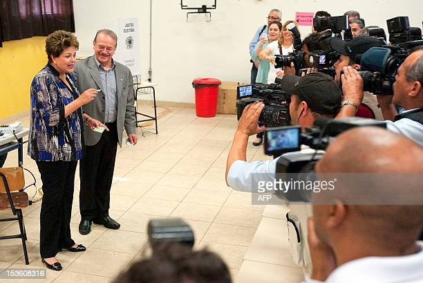 Brazilian President Dilma Rousseff accompanied by the governor of the southern Brazilian state of Rio Grande do Sul Tarso Genro speaks to the press...
