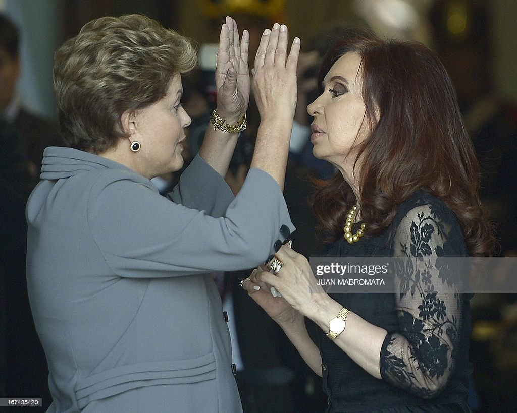 Brazilian President Dilma Rousseff (L) and Argentine President Cristina Fernandez de Kirchner talk before a working meeting at the Government Palace in Buenos Aires on April 25, 2013. Rousseff is on a one-day oficial visit to Argentina. AFP PHOTO / Juan Mabromata